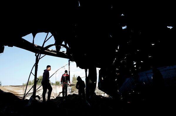 Палестинцы осматривают мечеть, которая была повреждена в результате израильского авиаудара в Газе