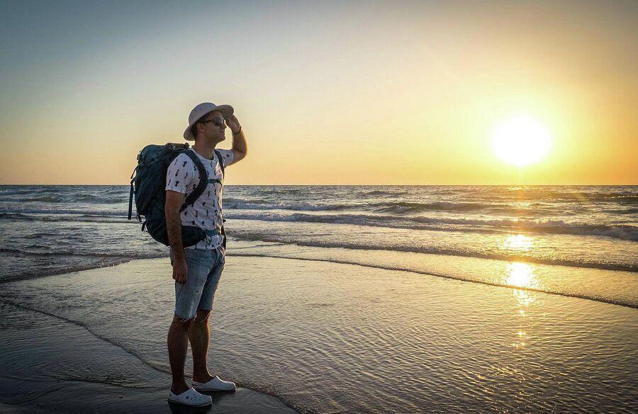 Александр Беленький на пляже с рюкзаком
