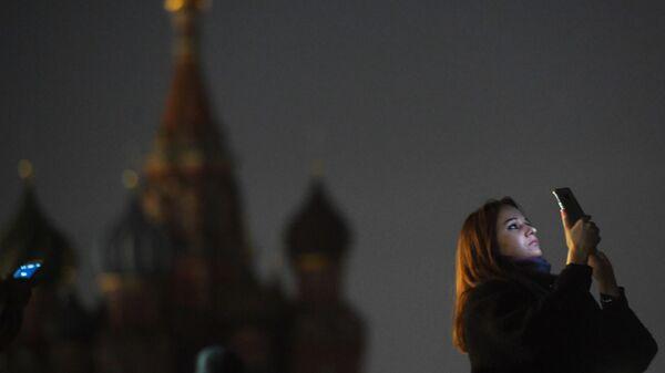 Девушка на Красной площади в Москве во время отключения подсветки в рамках экологической акции Час Земли