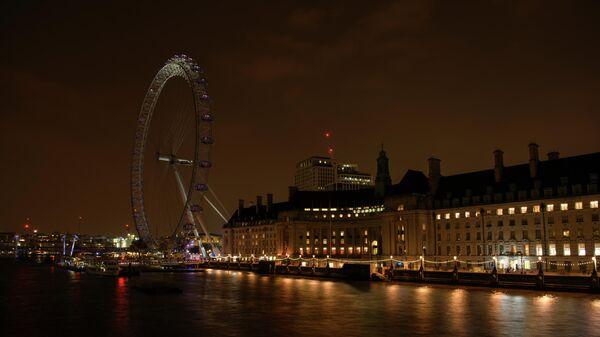 Колесо обозрения Лондонский глаз на набережной Темзы после отключения подсветки в рамках экологической акции Час Земли
