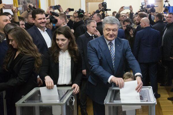 Действующий президент Украины Петр Порошенко с дочерьми на избирательном участке в Киеве во время голосования на президентских выборах.