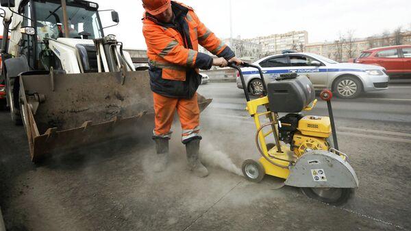 Рабочий проводит латочный ремонт дорожного покрытия