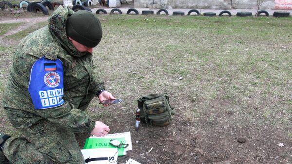 Офицер СЦКК фиксирует попадание снаряда в поселке Гольмовский города Горловка. 2 апреля 2019