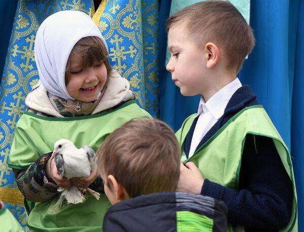 Дети готовятся выпустить голубей в небо над Соборной плщадью после богослужения в праздник Благовещения Пресвятой Богородицы в Благовещенском соборе Московского Кремля