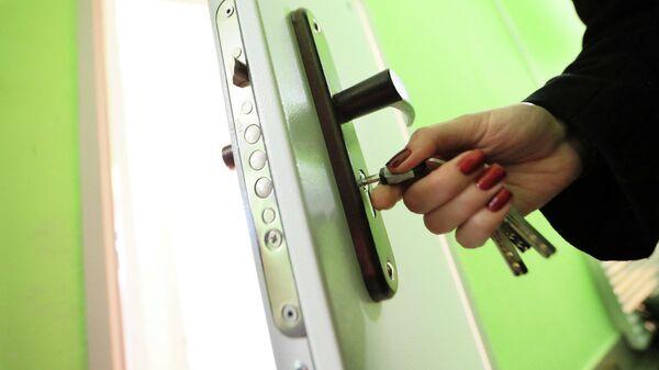 Женщина открывает дверь в квартиру