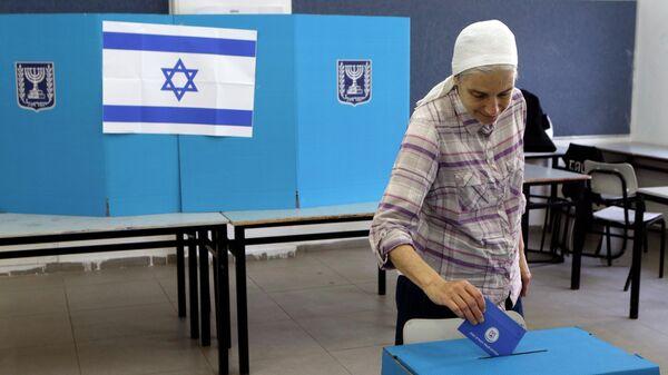 Женщина голосует на одном из избирательных участков в городе Тель-Авив в Израиле