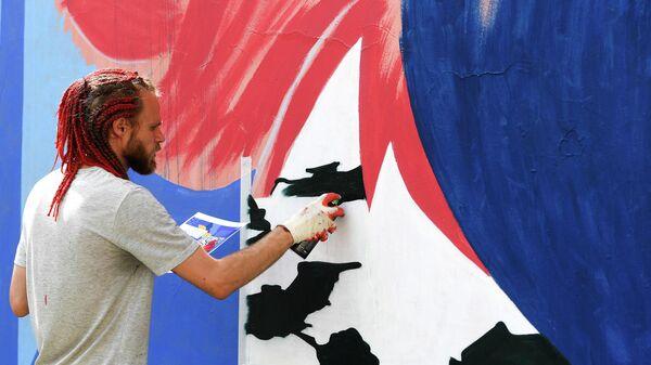 Художник рисует граффити