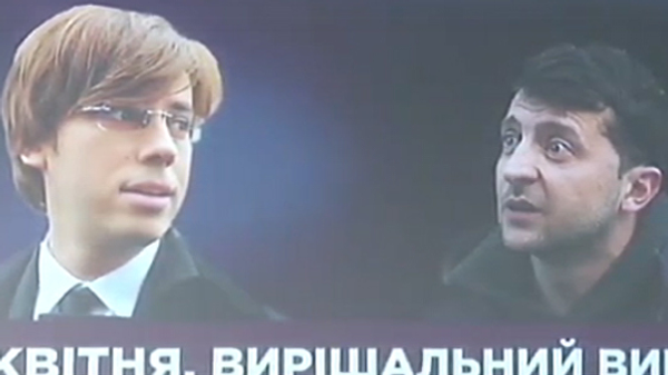 Билборд с фотографимями Галкина и Зеленского. Стоп-кадр трансляции брифинга представителя штаба президента Олега Медведева. 10 апреля 2019