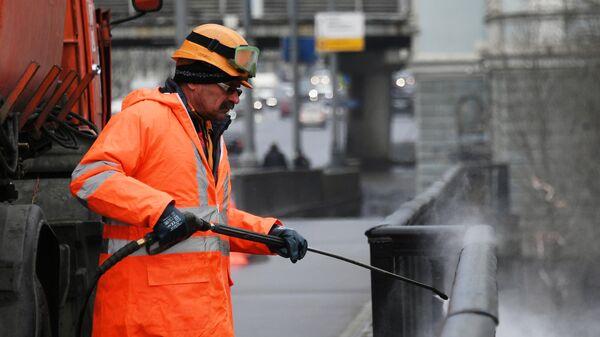 Сотрудник коммунальной службы моет ограду моста в Москве