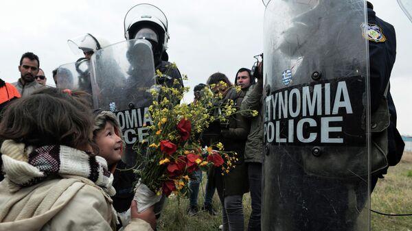 Дети дарят цветы сотрудникам полиции после беспорядков в лагере мигрантов в Диавате, Греция