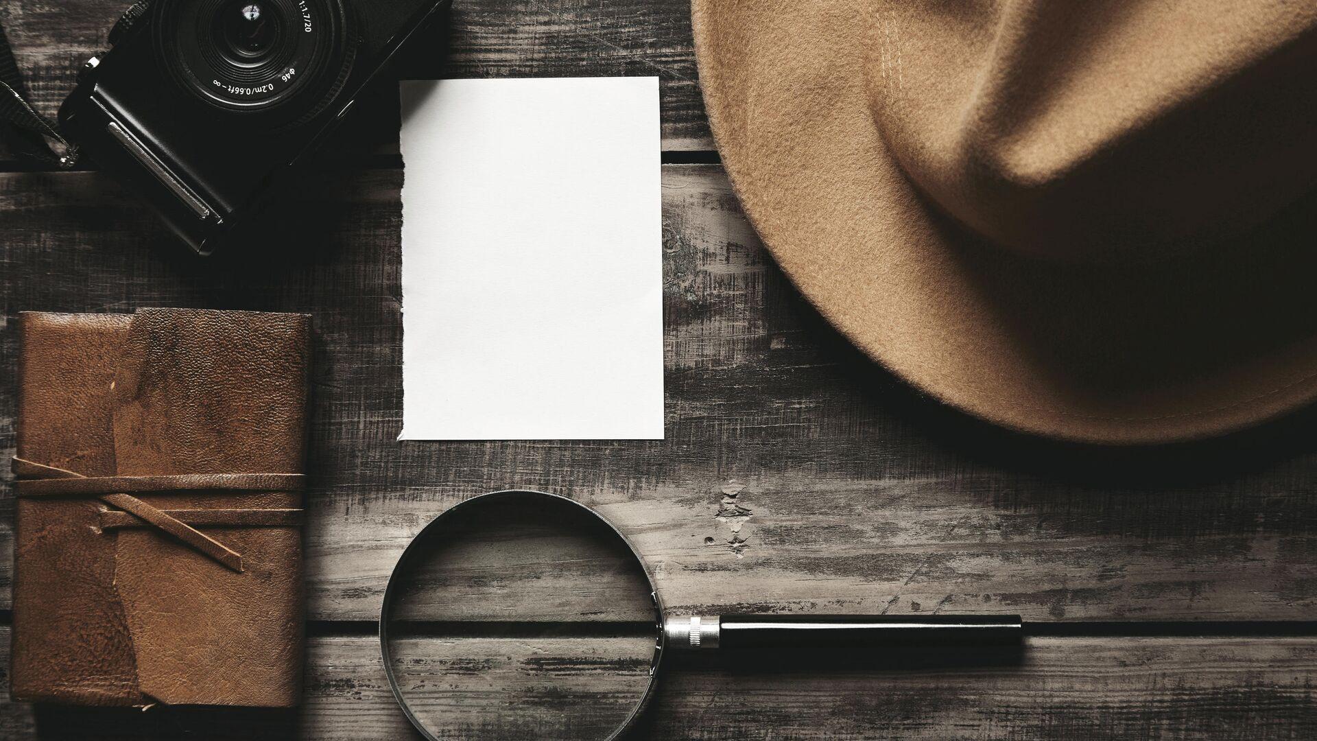 Закрытый блокнот в кожаном переплете, лист белой бумаги, фетровая шляпа, портативная  фотокамера и большая лупа на деревянном столе - РИА Новости, 1920, 04.02.2021