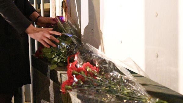Девушка возлагает цветы у посольства Франции в связи с пожаром в соборе Парижской Богоматери