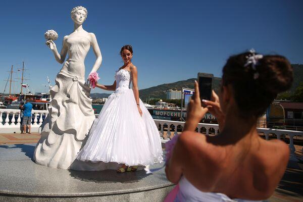 Участница карнавала фотографируется возле памятника Белая невеста на набережной Геленджика