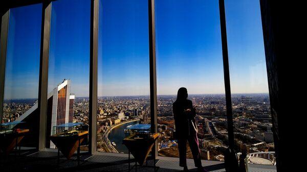 Посетительница смотровой площадки PANORAMA360, расположенной на 89-м этаже башни Федерации международного делового центра Москва-Сити