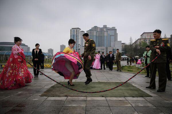 Жених и невеста прыгают через скакалку во время свадебной фотосессии в Пхеньяне