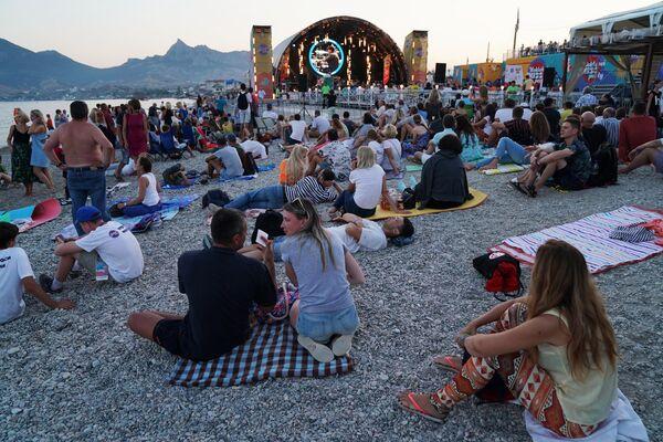 Люди расположились на пляже недалеко от главной сцены международного музыкального фестиваля Koktebel Jazz Party