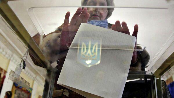 Женщина голосует на избирательном участке во время президентских выборов в Киеве, Украине