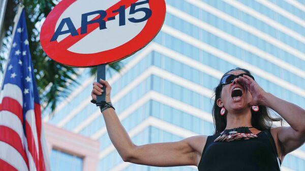 Девушка с плакатом против использования винтовки AR-15 во время акции протеста против ношения оружия в США