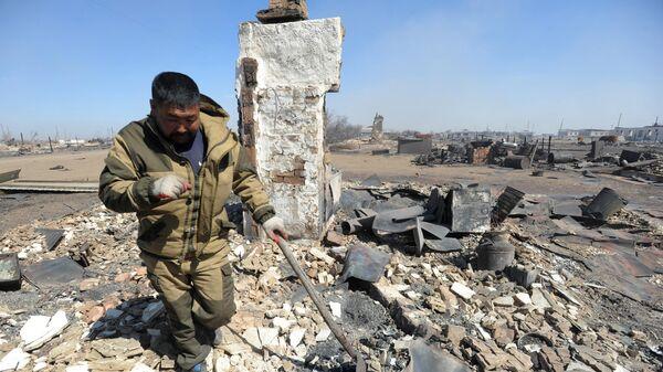 Мужчина ликвидирует последствия пожара в селе Усть-Ималка Ононского района Забайкальского края