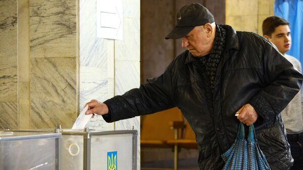 Мужчина во время голосования на одном из избирательных участков города Харькова в день второго тура выборов президента Украины