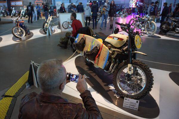 Посетитель фотографирует мотоцикл на Международном мотосалоне IMIS в Санкт-Петербурге