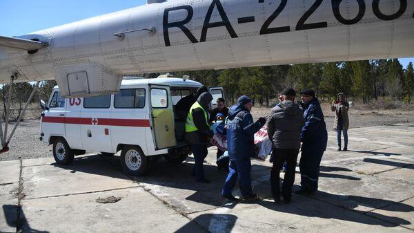 Транспортировка пострадавшего от пожара в селе Усть-Ималка в вертолет санитарной авиации для доставки в больницу Читы