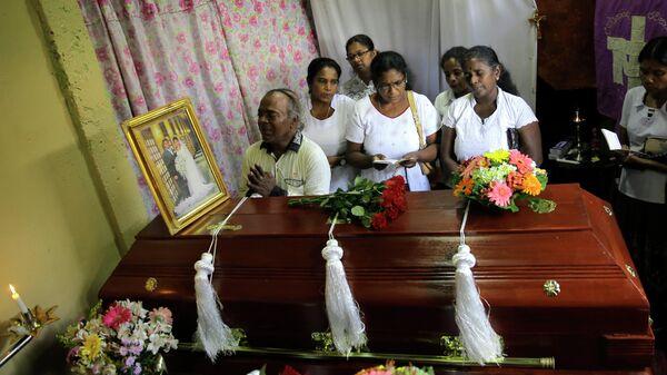 Семья скорбит рядом с гробом родственника, погибшего во время взрывов в пасхальное воскресенье в Коломбо, Шри-Ланка. 23 апреля 2019