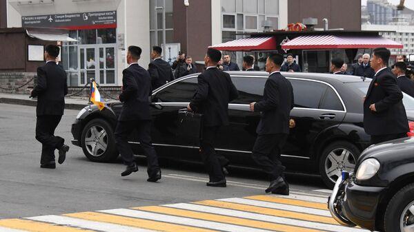 Сотрудники службы безопасности сопровождают автомобиль кортежа лидера КНДР Ким Чен Ына во Владивостоке