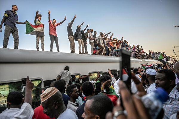 Суданские демонстранты из города Атбара на крыше поезда на железнодорожной станции Бахари в Хартуме