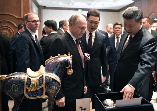 Президент РФ Владимир Путин и председатель КНР Си Цзиньпин обмениваются подарками после рабочего завтрака