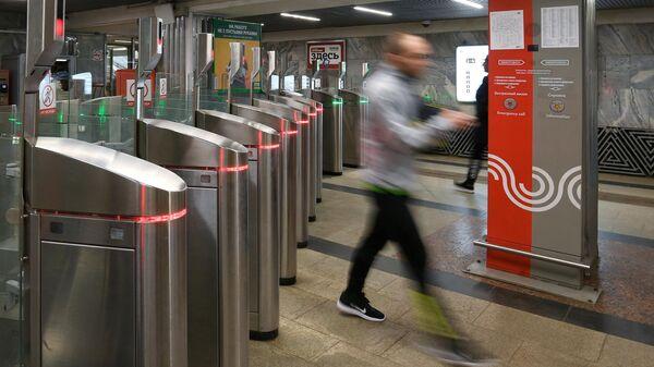 Пассажир московского метро проходит через турникеты на станции Октябрьское Поле