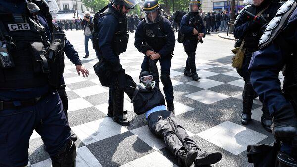 Полицейские задерживают демонстранта на первомайской демонстрации в Париже. 1 мая 2019