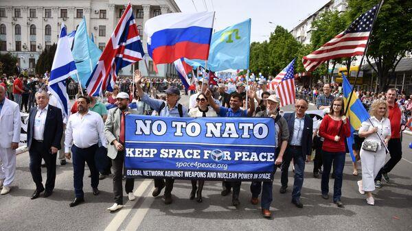 Представители зарубежных стран несут транспарант с надписью Нет НАТО во время первомайского шествия в Симферополе