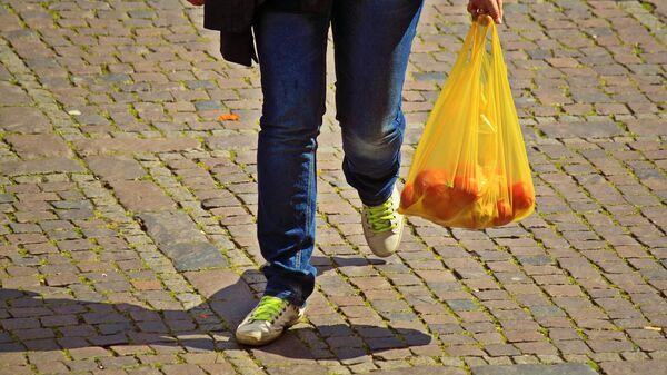 Покупатель с продуктами в пластиковом пакете