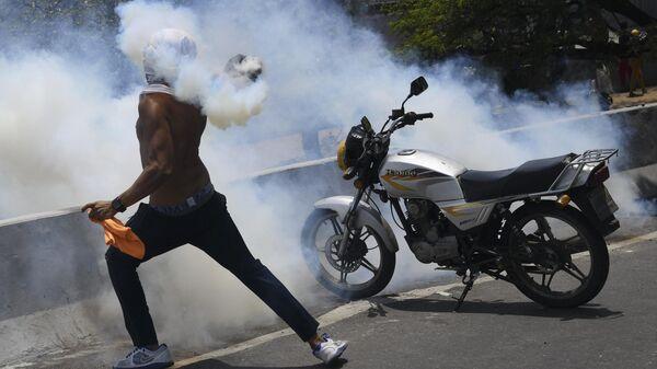 Протестующий кидает бутылку со слезоточивым газом во время столкновения с Национальной гвардией Венесуэлы в Альтамире, районе Каракаса.  Архивное фото