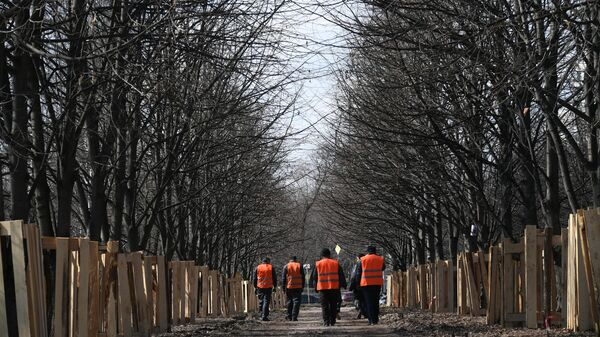 Работники коммунальных служб идут по территории, прилегающей к реке Яузе.