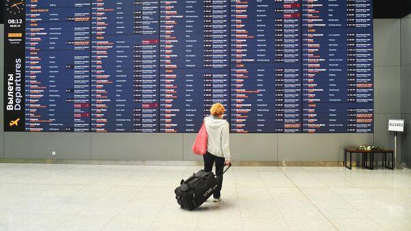 Женщина возле информационного табло с расписанием рейсов в аэропорту Шереметьево