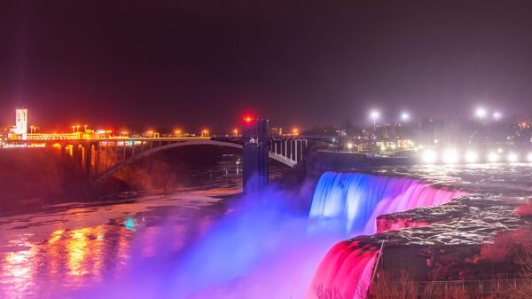 Вечерний вид на Американский водопад и Радужный мост со стороны Государственного парка Ниагарского водопада в штате Нью Йорк, США