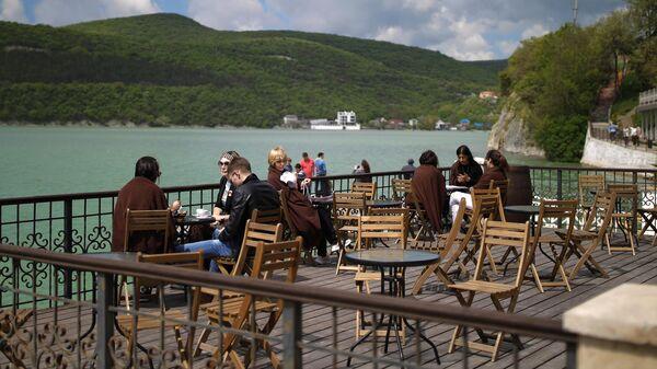 Отдыхающие на террасе летнего кафе в селе Абрау-Дюрсо на берегу озера Абрау в Краснодарском крае