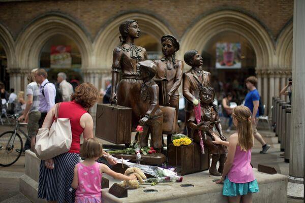 Люди кладут цветы к мемориалу Киндертранспорт, расположенному на станции Ливерпуль-стрит в Лондоне