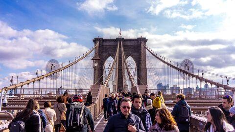Прохожие на Бруклинском мосту в Нью-Йорке
