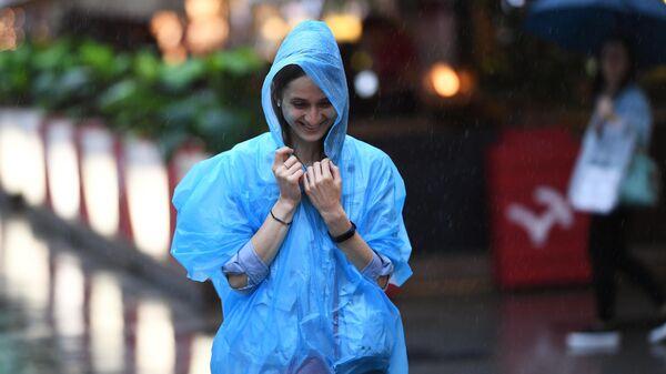 Девушка во время дождя на одной из улиц в Москве