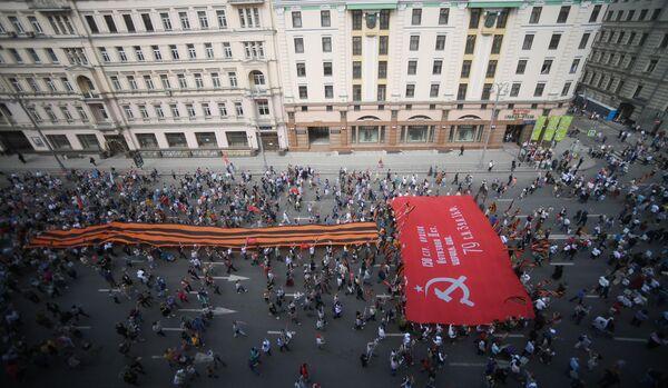 Участники акции Бессмертный полк в Москве несут гигантские георгиевскую ленту и Знамя Победы по Тверской улицы