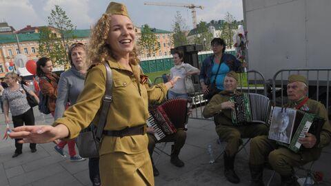 Девушка танцует под гармонь во время празднования Дня Победы в Москве