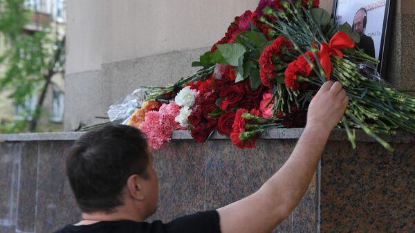 Мужчина возлагает цветы к зданию редакции Говорит Москва в память о главном редакторе радиостанции Сергее Доренко