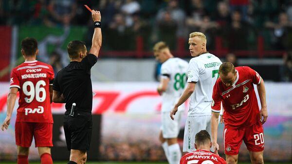 Владислав Безбородов (слева на первом плане) показывает красную карточку игроку Рубина Вячеславу Подберёзкину