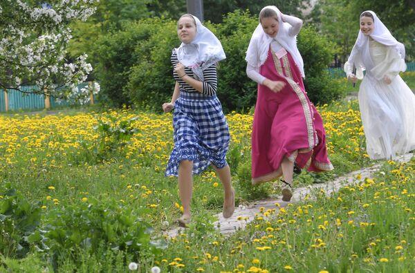 Девушки, бегущие в сарафанах и платках в день праздника Святых Жён-Мироносиц в духовном центре старообрядчества Рогожская слобода в Москве