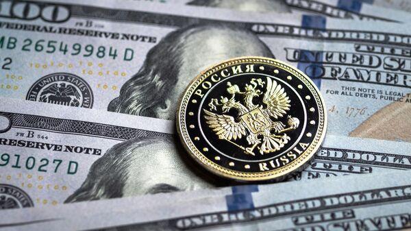 Купюры американских долларов и монета с гербом Российской Федерации