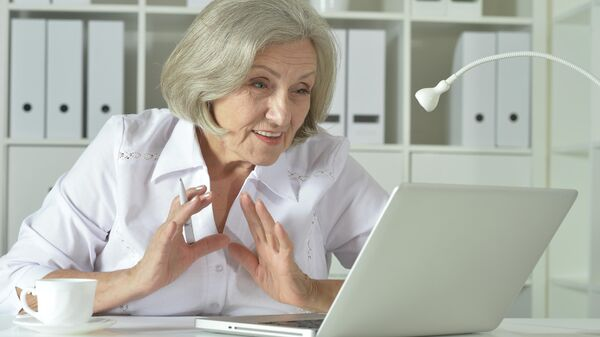 Пожилая женщина работает на ноутбуке