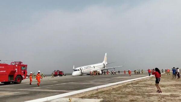 Эвакуированные пассажиры снимают лайнер Национальных авиалиний Мьянмы после жесткой посадки на брюхо в в международном аэропорту Мандалая